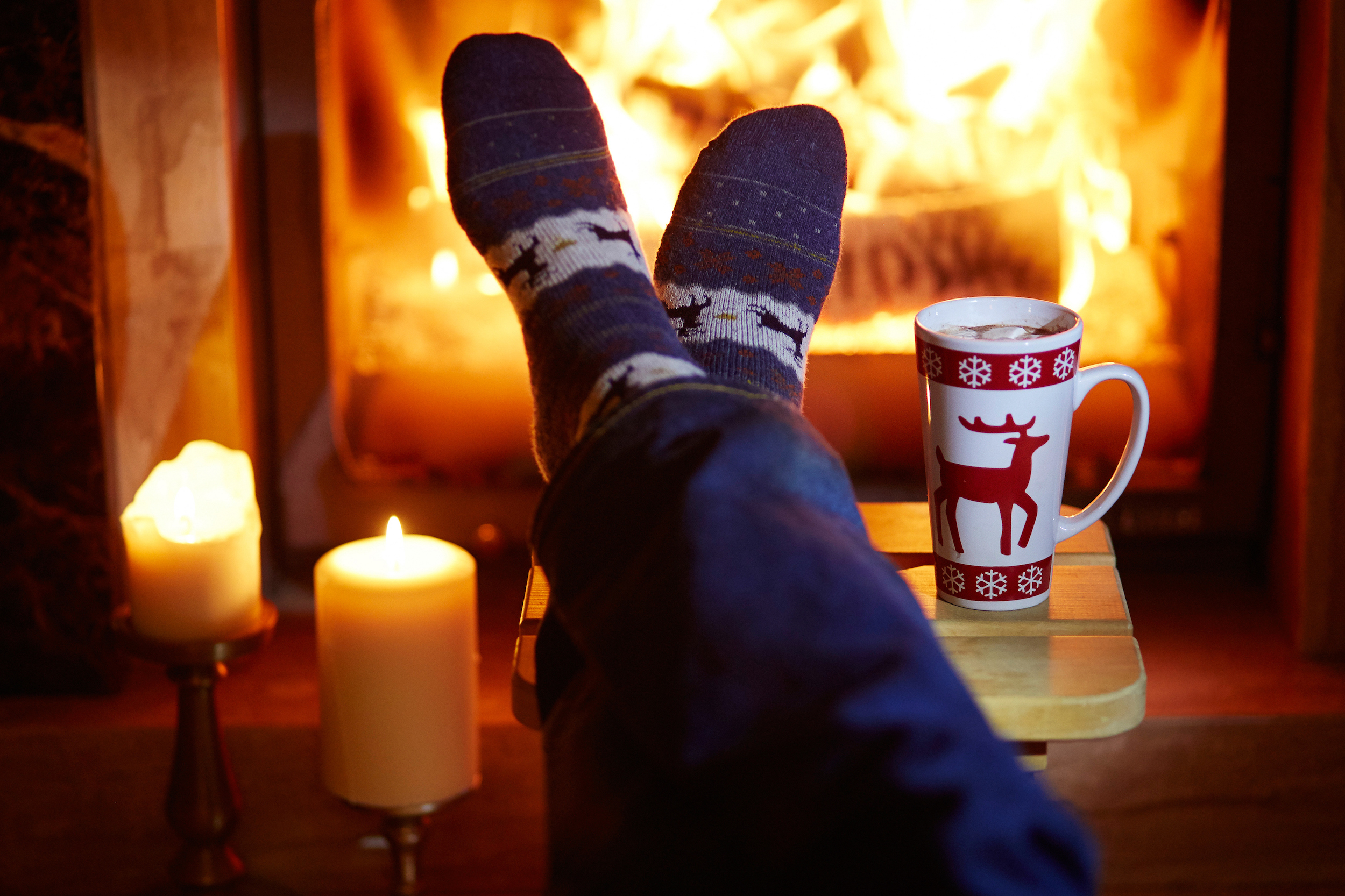 Man's feet in socks with large mug of hot chocolate by a clean fireplace thanks to Tiny Tom's Chimney Service and Repair